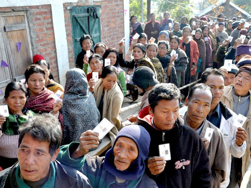 Voters wait in queues to cast their votes at a polling station during assembly polls at Motbung in Senapati district. PTI Photo