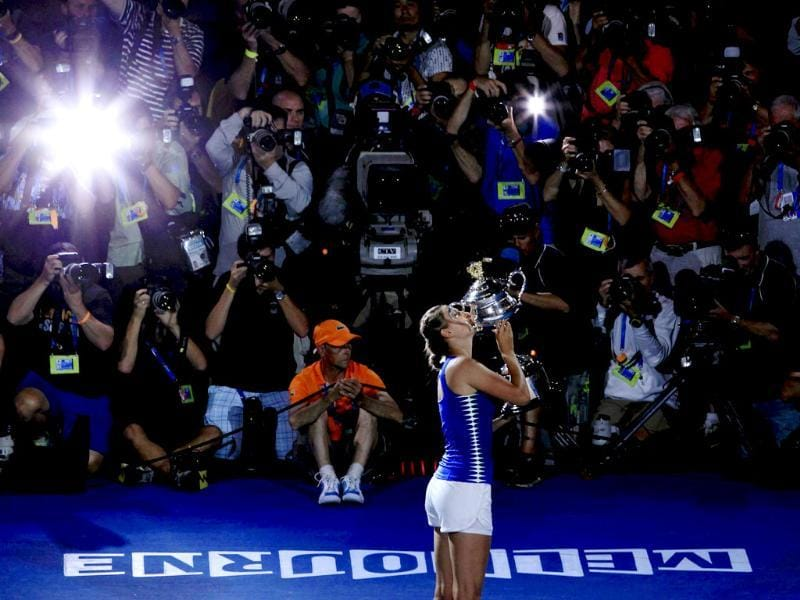 Victoria Azarenka kisses her trophy in front of photographers as she celebrates after defeating Maria Sharapova. Reuters/Darren Whiteside