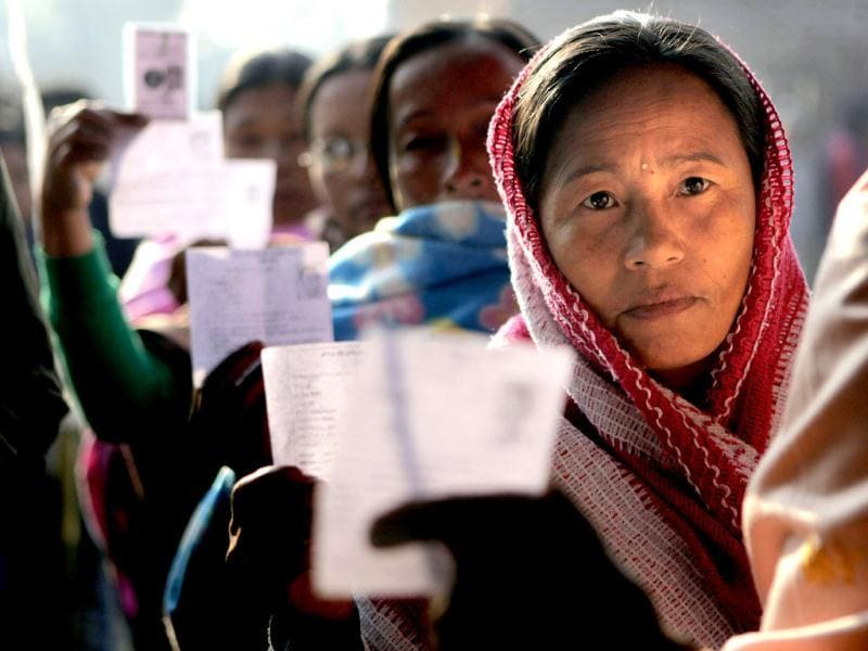 Women voters show their election cards as they stand queue to cast their votes in a polling station in Thoubal constituency on the outskirts of Imphal. AP Photo/Anupam Nath