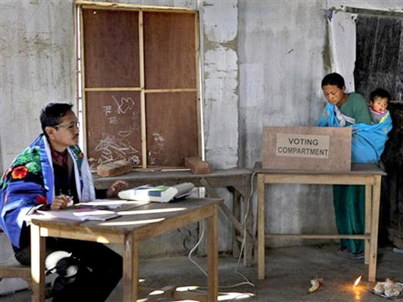 A woman with her child casts her vote at a polling station in Thoubal constituency on the outskirts of Imphal. AP Photo/Anupam Nath