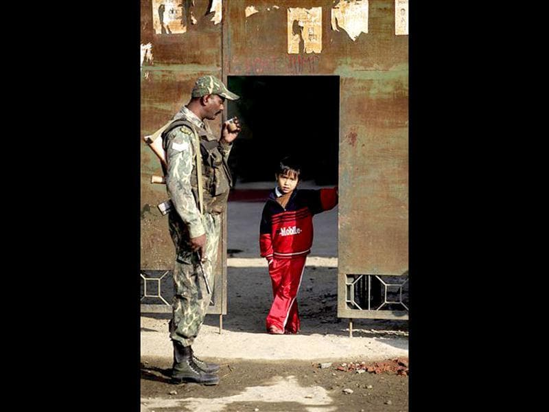A para-military force soldier sips tea as a child looks on inside a polling station in Thoubal constituency on the outskirts of Imphal. AP Photo/Anupam Nath