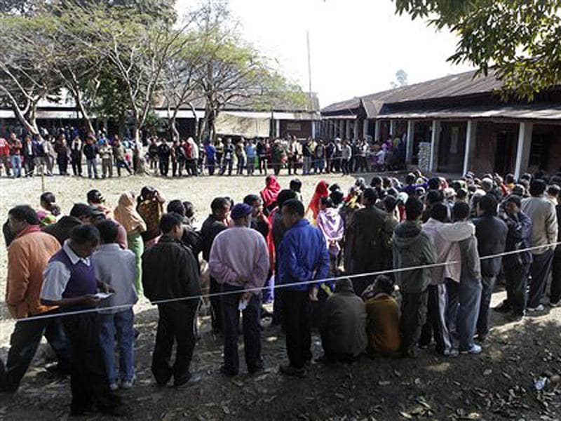 People stand in queue to cast their votes at a polling station in Sekmai constituency on the outskirts of Imphal. AP Photo/Anupam Nath