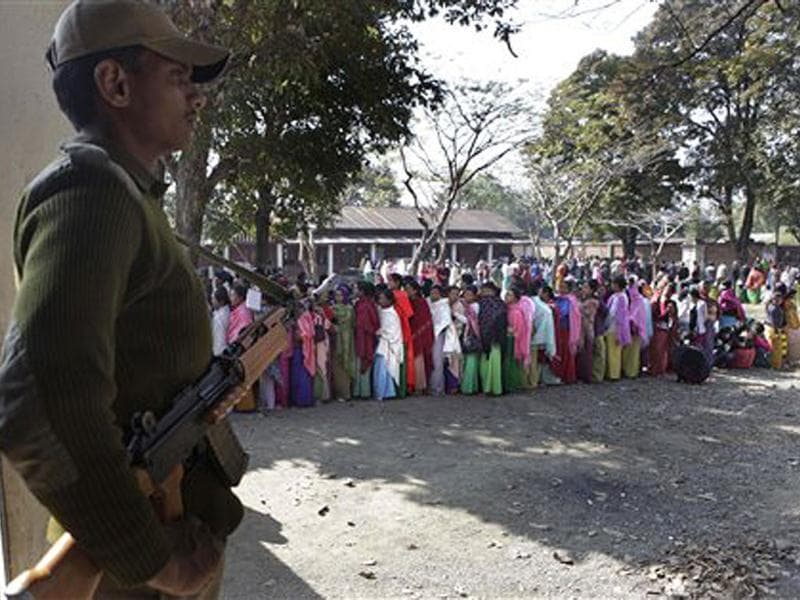 A para-military force solder stands guard as women voters stand in a queue to cast their votes at a polling station in Thoubal constituency on the outskirts of Imphal. AP Photo/Anupam Nath