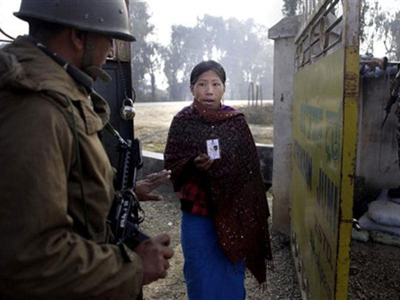 A woman shows her election card as she enters a polling station in Thoubal constituency on the outskirts of Imphal. AP Photo/Anupam Nath