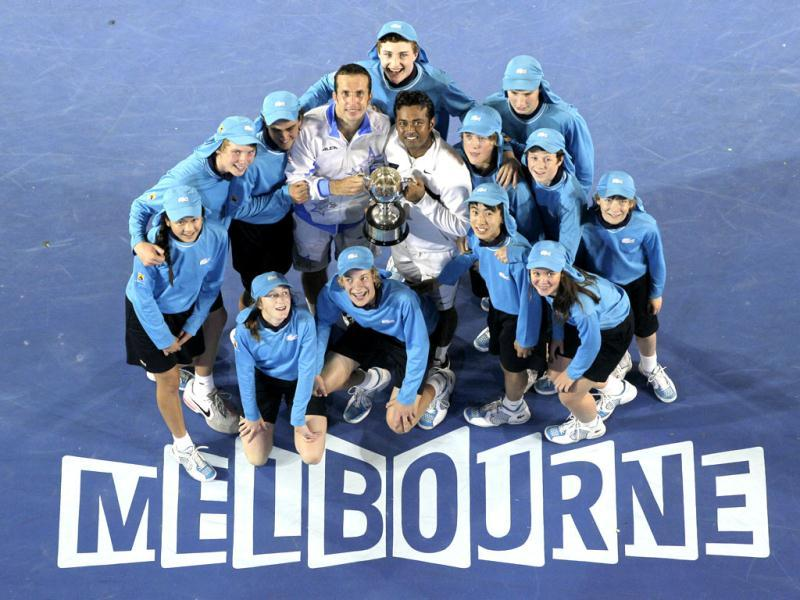 Leander Paes and Radek Stepanek of the Czech Republic hold the trophy, surrounded by ball boys and girls during the awarding ceremony after defeating USA's Bob Bryan and Mike Bryan in their men's doubles final at the Australian Open tennis championship, in Melbourne. (AP Photo/John Donegan)