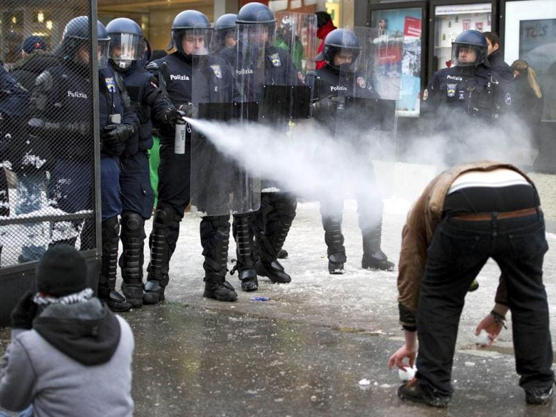 Swiss riot police spray tear gas against a member of