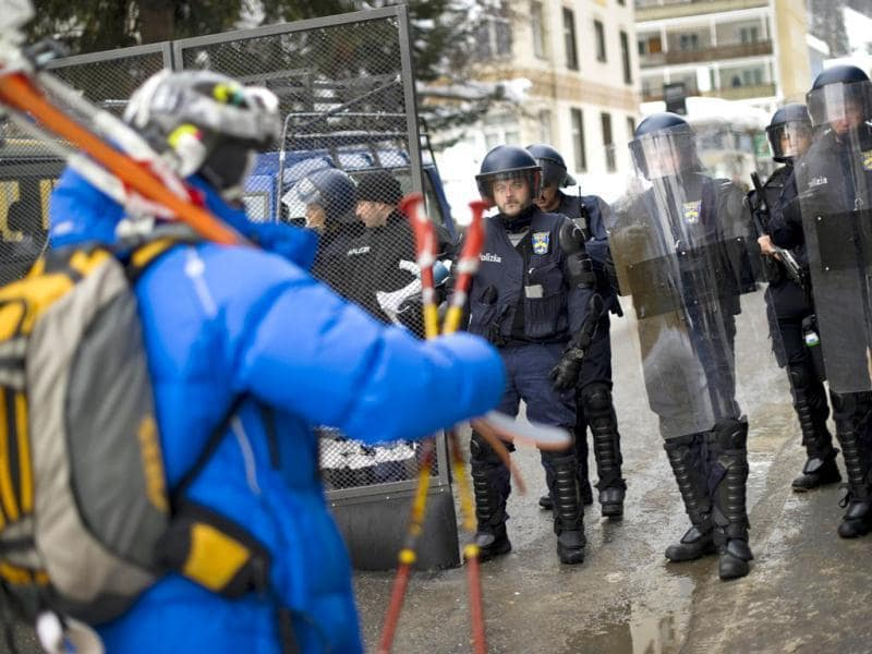 A skier walks past Swiss riot police officers during a demonstration. (AFP PHOTO / FABRICE COFFRINI )