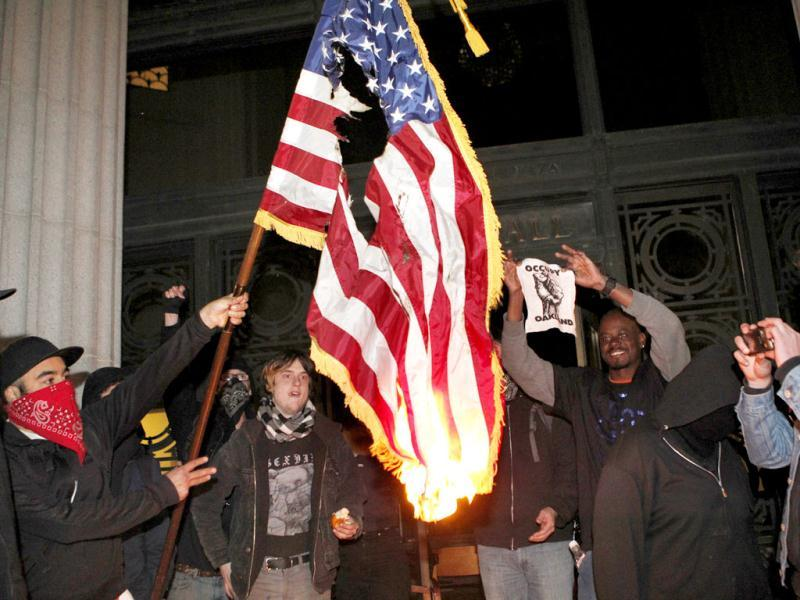 Occupy Oakland protestors burn an American flag found inside Oakland City Hall during an Occupy Oakland protest on the steps of City Hall in Oakland, Calif. AP