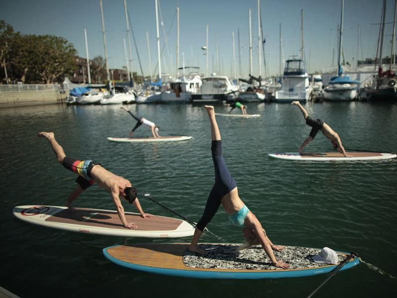 Instructor Sarah Tiefenthaler (front) demonstrates a pose during her Yogaqua class, which combines yoga and paddleboarding, in Marina Del Rey, Los Angeles. (REUTERS/Lucy Nicholson)