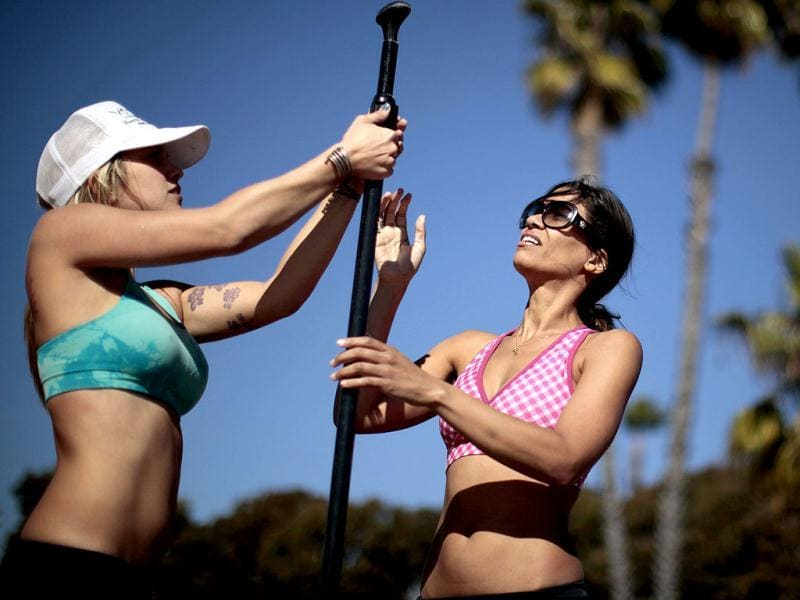 Instructor Sarah Tiefenthaler (L) adjusts a paddle for Chelsea McElroy, 40, during her Yogaqua class, which combines yoga and paddleboarding, in Marina Del Rey, Los Angeles. (REUTERS/Lucy Nicholson)