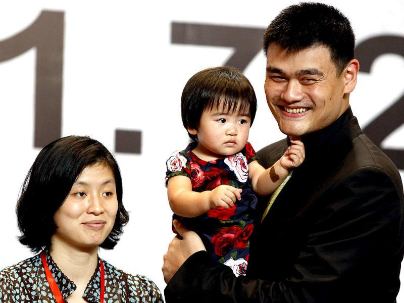 NBA player Yao Ming holds his daughter Qin Lei next to his wife Ye Li during a news conference to announce his retirement from basketball, in Shanghai. (Reuters)