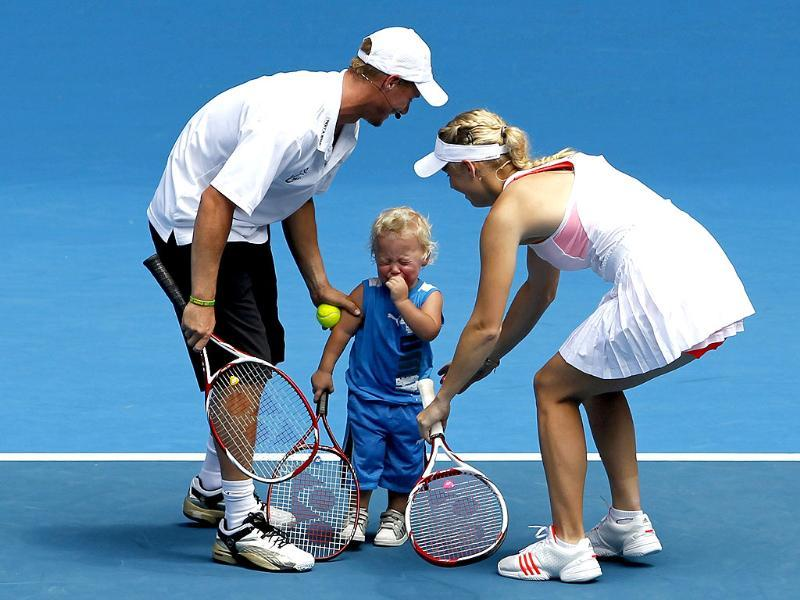 Caroline Wozniacki of Denmark plays with Cruz, the son of Lleyton Hewitt of Australia, during a Rally for Relief tennis match to raise money for victims of Australia's flood disaster ahead of the Australian Open in Melbourne. (Reuters)