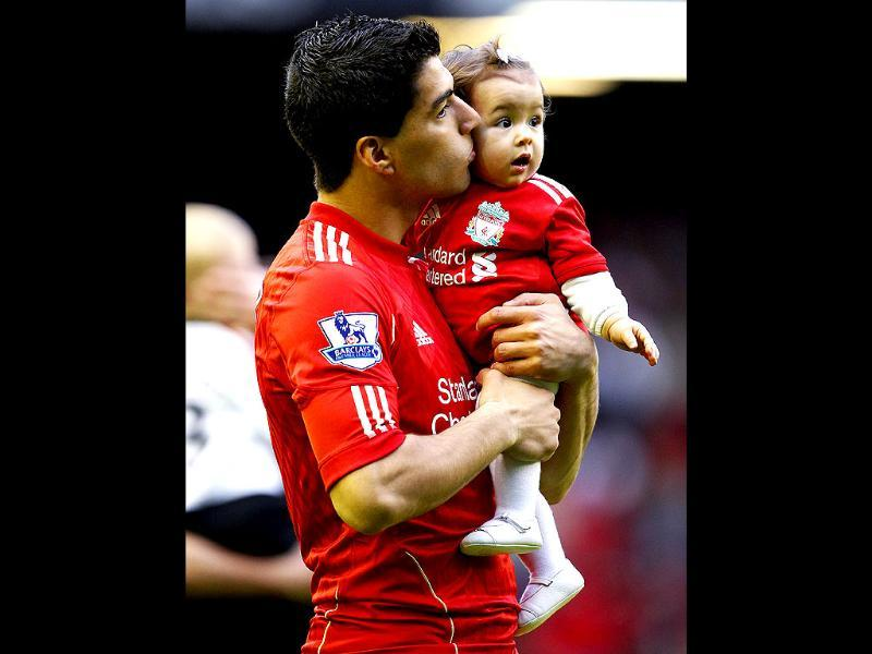 Liverpool's Luis Suarez kisses his daughter as he walks around the pitch following their English Premier League soccer match against Tottenham Hotspur at Anfield in Liverpool. (Reuters)