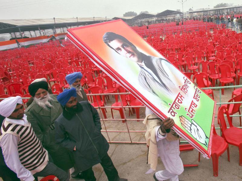 A supporter of Congress party carries billboards of Rahul Gandhi after an election campaign rally ahead of state assembly elections at Moga in Punjab. (Reuters)