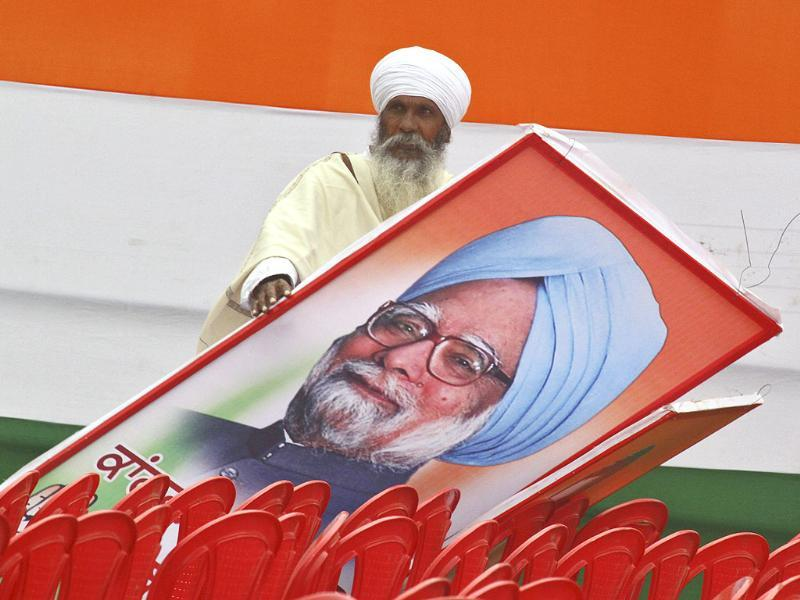 A supporter of Congress party holds a billboard of Prime Minister Manmohan Singh after an election campaign rally ahead of state assembly elections at Moga, Punjab. (Reuters)