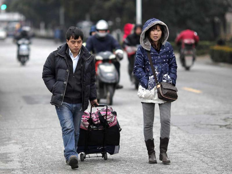 Workers walk with their belongings as they return to work after the Chinese New Year holidays in Shanghai. Reuters/Carlos Barria