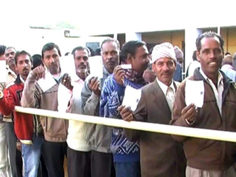 Voters show their election card before casting their votes during the assembly elections in Uttarakhand. (ANI Photo)