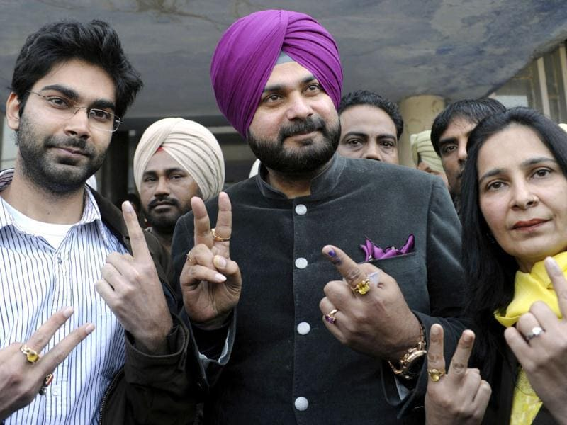 Former cricketer and member of parliament Navjot Singh Sidhu (C) and wife Bhartiya Janata Party (BJP) candidate for the Member of Legislative Assembly (MLA) Navjot Kaur Sidhu (R), and their son Karan Sidhu (L) display their fingers marked with indelible ink after casting their ballots at a polling station in the outskirts of Amritsar. Voters braved cold weather to cast ballots in the breadbasket state of Punjab in a local election seen as a test of popularity of India's embattled ruling Congress party. AFP Photo/Narinder Nanu