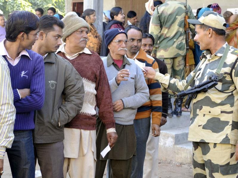 An Indian Border Security Force (BSF) soldier checks the identity card of a voter as others stand in a queue to cast their vote at a polling station in the outskirts of Amritsar. Voters braved cold weather to cast ballots in the breadbasket state of Punjab in a local election seen as a test of popularity of India's embattled ruling Congress party. AFP Photo/Narinder Nanu