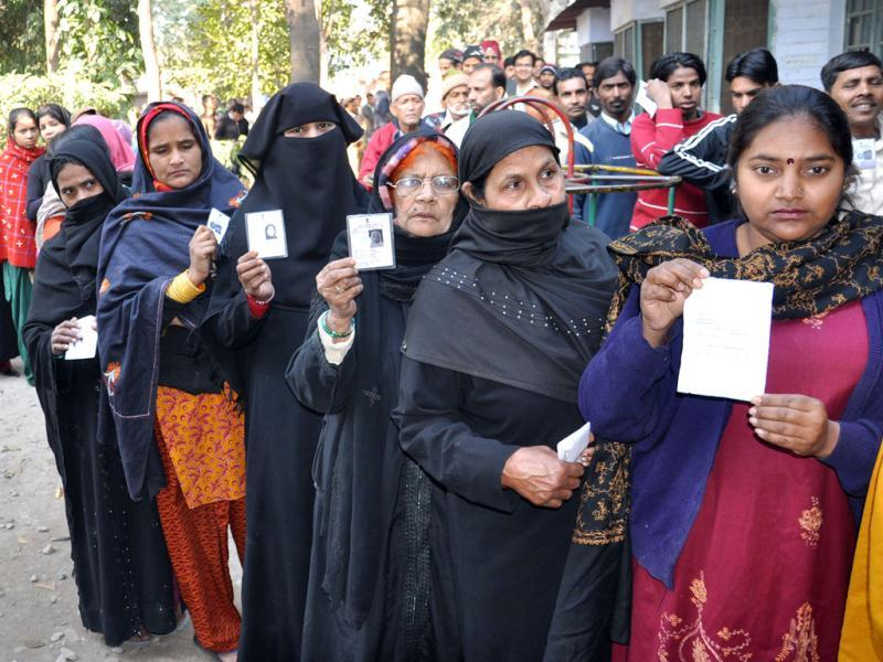 Burqa clad Muslim women show their voter ID card while lined up outside a polling station to cast their vote during Uttarakhand Assembly polls, in Dehradun. UNI Photo