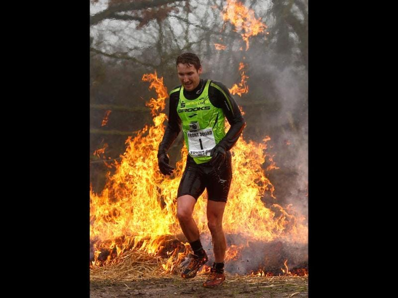A competitor runs through flames at the annual Tough Guy event, Perton, England. (AP Photo/Jon Super)
