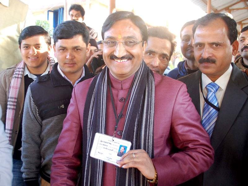 Former Uttarakhand chief minister Ramesh Pokhriyal Nishank shows his identity card and the ink marked finger after casting his vote in Uttrakhand Assembly polls, at a polling station in Dehradun. UNI Photo