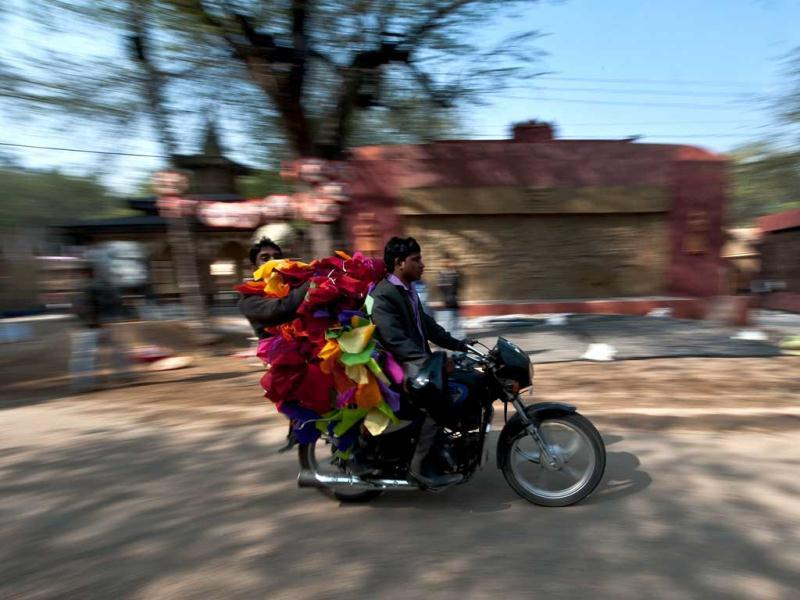 Two men carry decorative items on a motorcycle ahead of the annual Surajkund Crafts Fair in Surajkund, some 25kms from New Delhi. AFP Photo/Manan Vatsyayana