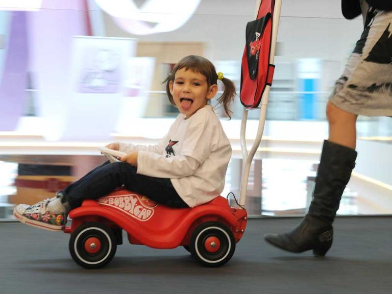 A girl poses at a Bobby car during the press preview of the international toy fair in Nuremberg, southern Germany. AFP