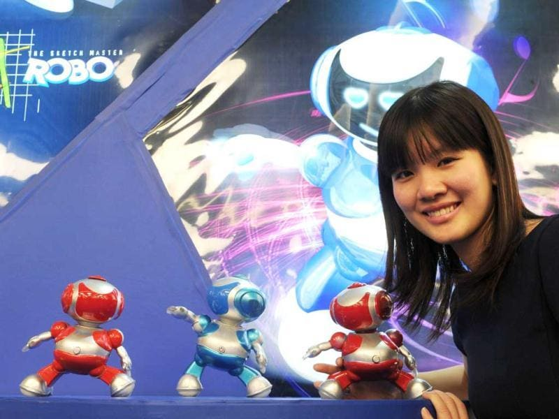 A young girl poses beside robots of an exhibitor from Vietnam at the press preview of the international toy fair in Nuremberg, southern Germany. AFP