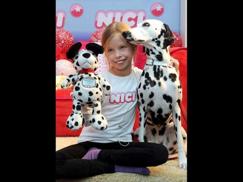 A young girl poses beside a dalmatian and a plush toy alarm clock during the press preview of the international toy fair in Nuremberg, southern Germany. AFP