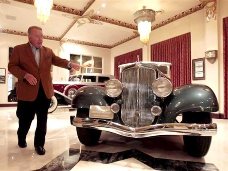 Bob Milhous shows a 1933 Chrysler Phaeton at the Milhous Collection in Boca Raton, Florida. One of America's most extraordinary and voluminous private collections of vintage cars, automated musical instruments and other memorabilia is going on the auction block. Brothers Bob and Paul Milhous will empty their 39,000-square-foot building, auctioning off its contents to bidders. The crown jewel is a custom-built carousel with 42 hand-carved animals, expected to fetch at least $1 million. All told, the auction is expected to generate about $40 million. (AP Photo/Alan Diaz)