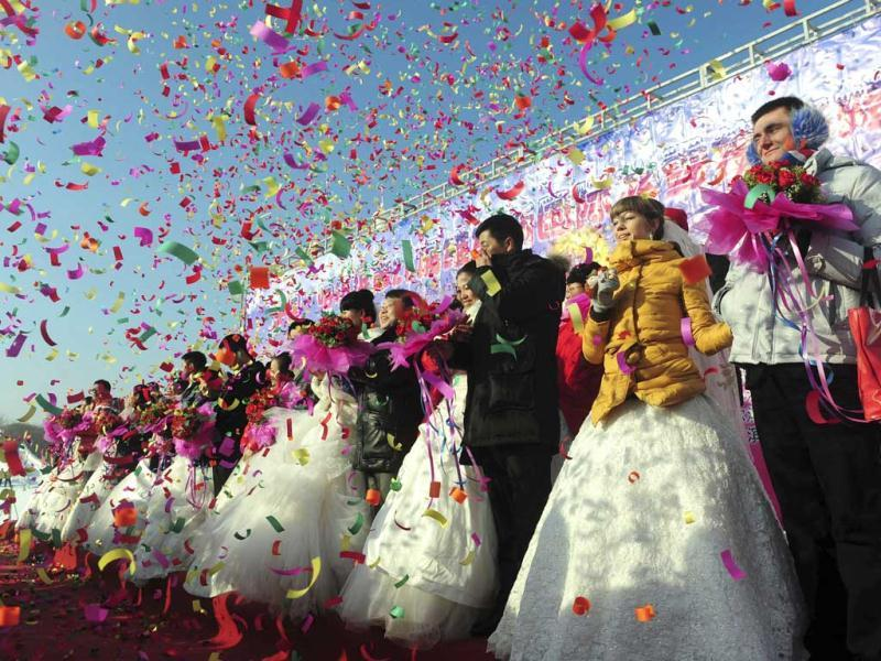 Confetti is thrown at couples during a group wedding ceremony as part of the 28th Harbin International Ice and Snow Festival in Harbin, Heilongjiang province. Reuters/Sheng Li