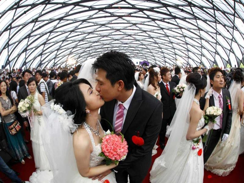 Zheng Ya-yuan (L), 32, and Chang Hong-chang, 31, who have been dating for six years, kiss during a mass wedding ceremony at the Taipei Flora Expo Hall. Reuters/Nicky Loh