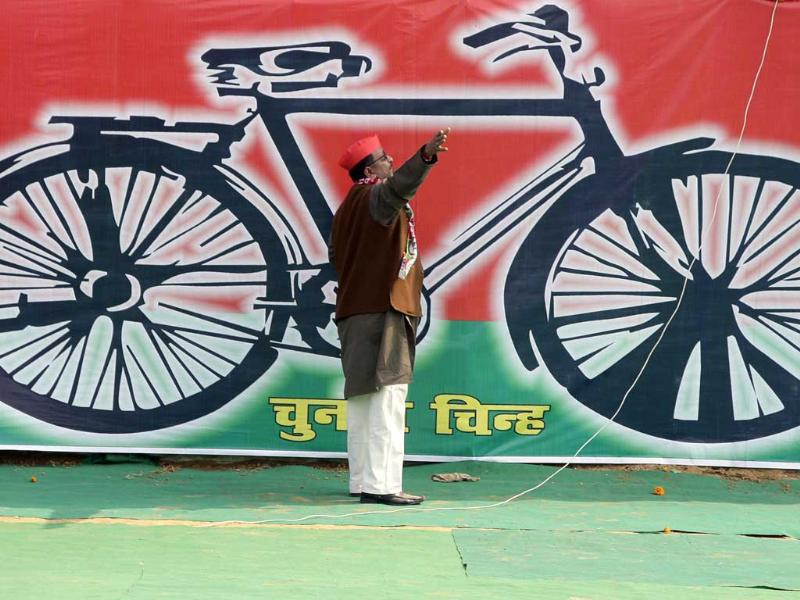 A Samajwadi Party worker gestures in front of a banner with the party's electoral symbol, the bicycle, during a campaign rally to be addressed by its president Mulayam Singh Yadav, ahead of state assembly elections in Allahabad. Reuters/Jitendra Prakash.