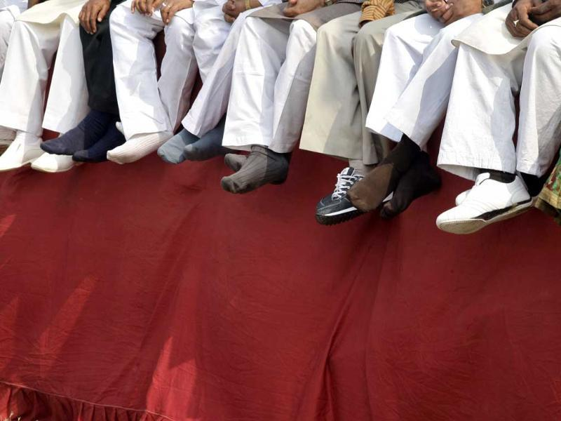 Samajwadi Party workers sit on a podium during an election campaign rally to be addressed by the party's president Mulayam Singh Yadav ahead of state assembly elections in the northern Indian city of Allahabad. Reuters/Jitendra Prakash.
