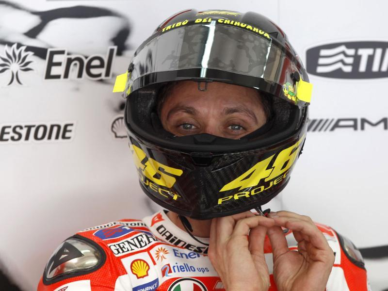 MotoGP rider Valentino Rossi from Italy adjusts his helmet during a pre-season test run at Sepang circuit in Malaysia. AP Photo/Vincent Thian