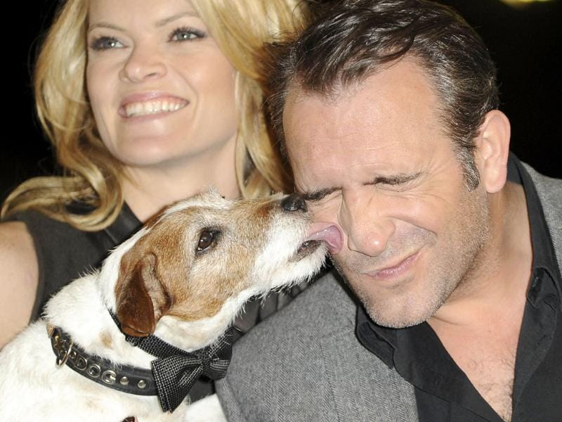 Actor Jean Dujardin (R) gets a kiss from Uggie the dog, held by actress Missi Pyle, at a ceremony honoring the cast and crew of The Artist with the Made In Hollywood in California. AFP Photo/Robyn Beck