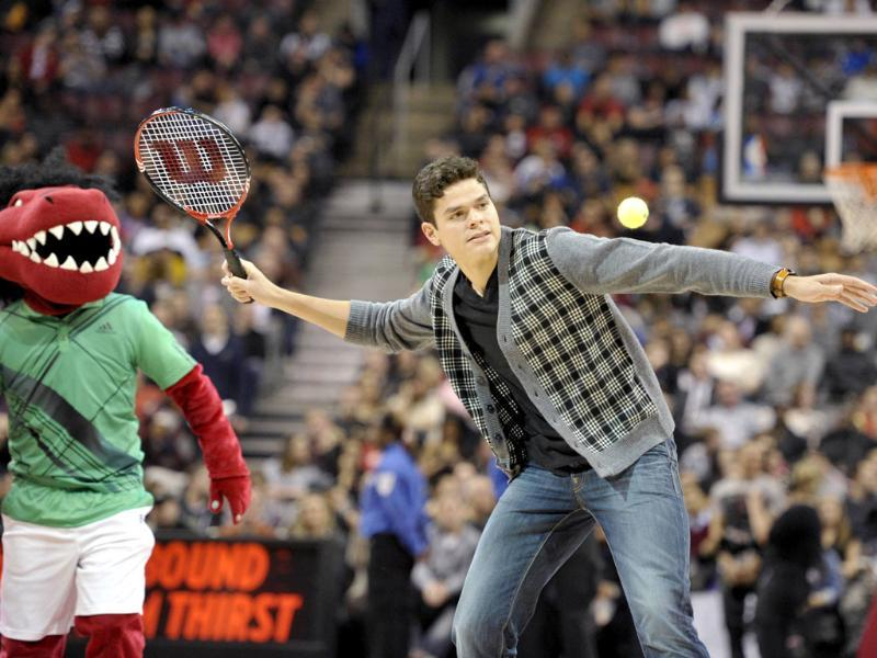 Canadian tennis player Milos Raonic hits tennis balls to fans during a time-out at the Toronto Raptors and Atlanta Hawks NBA basketball game in Toronto. Reuters/Mike Cassese
