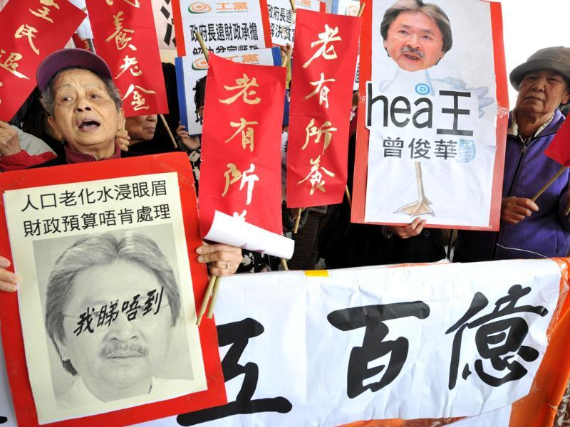Protesters shout slogans outside the Hong Kong Legislative Council prior to financial secretary John Tsang's 2012-2013 budget speech. AFP Photo/Aaron Tam
