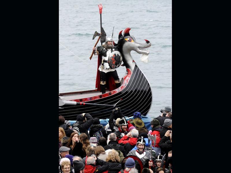 'Guizer Jarl' David Nicholson, leader of the 'Jarl Squad', stands aboard his longboat next to its beast-head prow during the annual Up Helly Aa festival in Lerwick, Shetland Islands. (AFP PHOTO/Andy Buchanan)