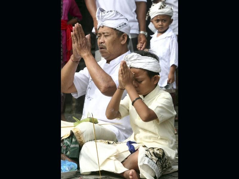 A Balinese father prays with his son during Hindu festival of Galungan, celebrating the triumph of good over evil at a temple in Denpasar, Bali, Indonesia. AP Photo/Firdia Lisnawati