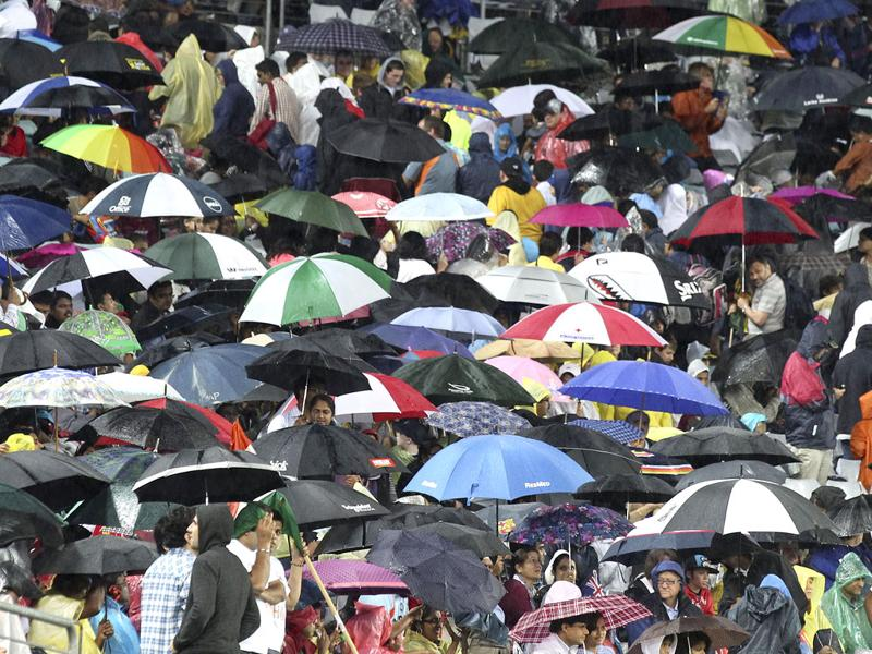 Fans hide under umbrellas as the rain pours down during the Twenty20 international cricket match between India and Australia in Sydney. AP Photo/Rob Griffith