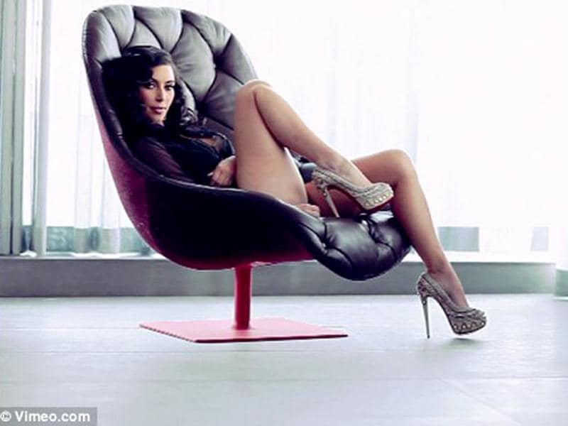 Seductress: Kim lounges in a leather chair.