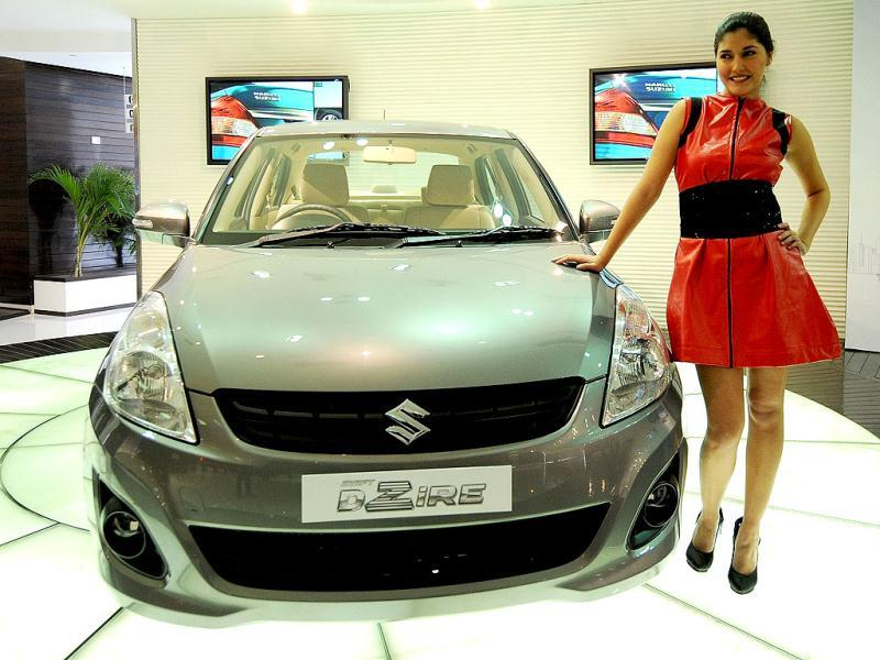 A model poses with the newly unveiled Swift DZire in New Delhi. Maruti Suzuki unveiled the all new compact, powerful and more fuel efficiant Swift DZire entry level sedan with K-12 VVT petrol engine and a D13A intercooler turbocharger DDiS diesel engine. AFP/Prakash Singh