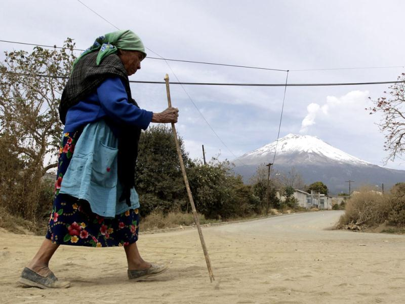 A local resident walks as the Popocatepetl volcano belches a column of steam in the Xalitzintla municipality in Puebla, located 125 km (78 miles) east of Mexico City. Civil protection officials from the Puebla government are giving evacuation training to residents of this village located 12 km (7 miles) from the Popocatepetl volcano, ahead of a possible eruption, after an increase of volcanic activity and ash eruptions have been registered recently.  Reuters/Henry Romero