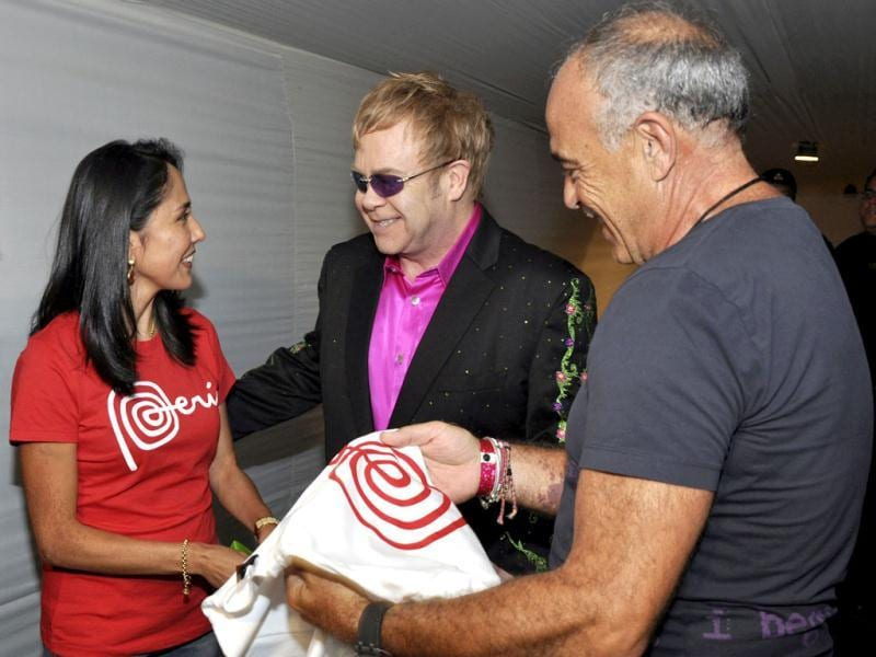 Peru's first lady Nadine Heredia (L) gives a t-shirt with Peru's country logo to British singer Elton John (C) before his concert in Lima. Elton John performed for the first time in Peru as part of his Latin America tour. Reuters/Peru Presidential Palace Press Office/Handout