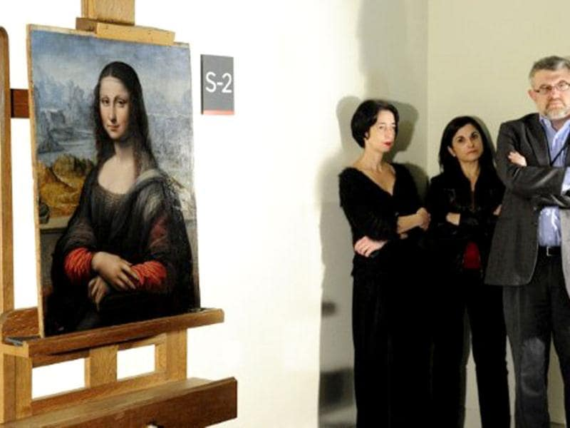 Prado Museum employees stand next to an authenticated contemporary copy of Leonardo da Vinci's Mona Lisa presented at the Prado Museum after it was found in its vaults. According to details of experts' findings published by the specialist British journal The Art Newspaper and the Spanish media, the work is a copy painted in Da Vinci's studio by one of his pupils. AFP Photo / Javier Soriano