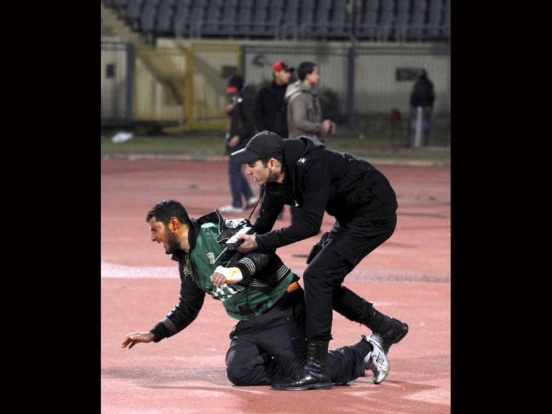 A policeman arrests an injured rioting soccer fan as chaos erupts at a soccer stadium in Port Said city, in Egypt. Seventy-three people were killed and at least 1,000 injured on Wednesday after a soccer pitch invasion in the Egyptian city of Port Said, a health ministry official said, in an incident that one player described as