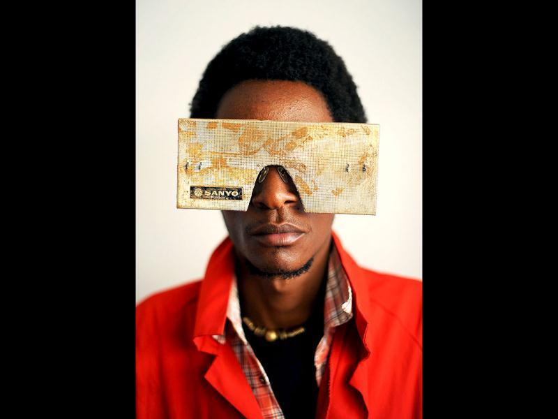 Kenyan artist Cyrus Kabiru poses with an artwork resembling sunglasses in Nairobi. AFP