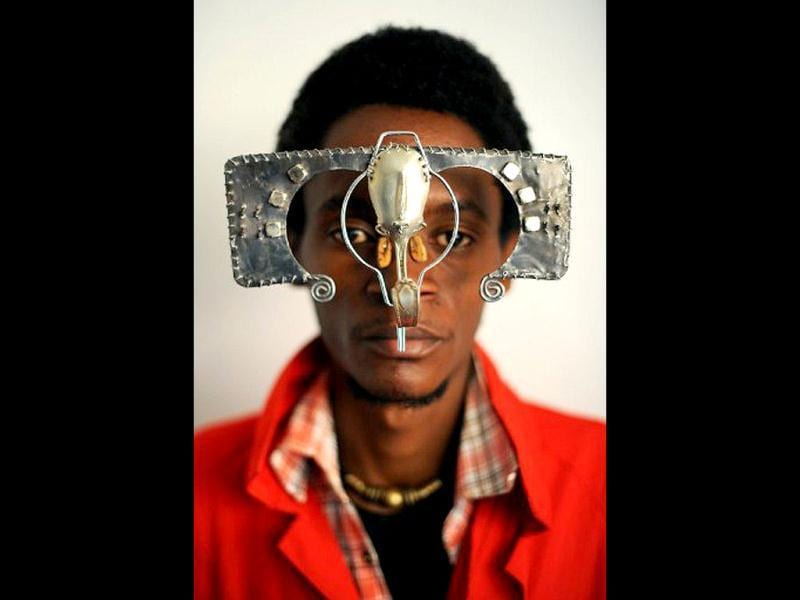 Kenyan artist Cyrus Kabiru poses with an artwork resembling sunglasses in Nairobi. Kabiru has created a range of artworks called